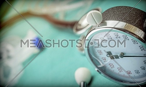 White pad next to a manometer to measure blood pressure and a stethoscope in a hospital, conceptual image