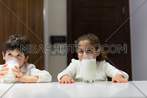 little middle east boy and girl eating snacks and drinking milk in the kitchen with pleasure