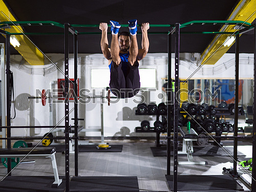 young muscular man doing pull ups on the horizontal bar as part of Crossfitness Training