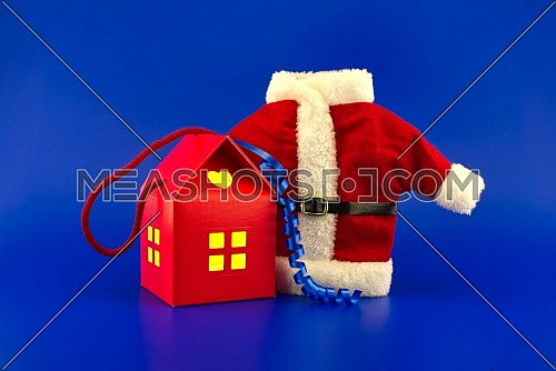 House shaped gift box with yellow glowing windows and red Santa Claus suit on a blue background. New Year and Christmas holiday season concept card decoration