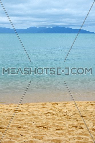 Footprints on sand beach shore over blue sea and cloudy sky background