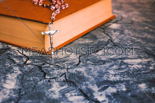 Silver rosary and cross resting on the closed book at gray table,front view.religion school concept.Vintage style.