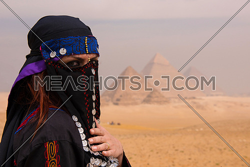 egyptian woman in traditional clothes in front of ancient giza pyramids