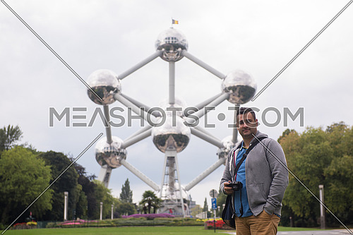 a portrait of a male tourist standing in front of Atomium building in Brussels