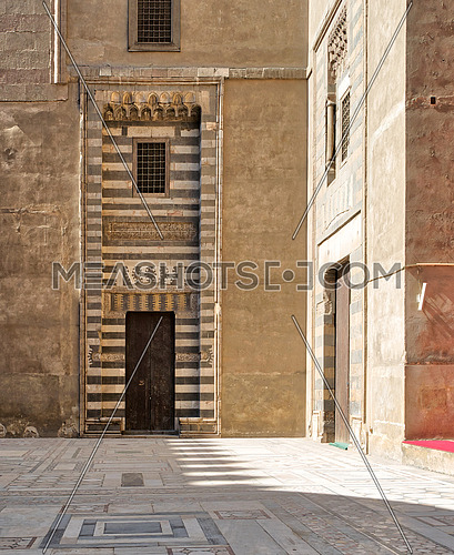 Wooden aged door surrounded by striped black and white marble decorations and stone wallat the courtyard of Sultan Hassan Mosque, Cairo, Egypt