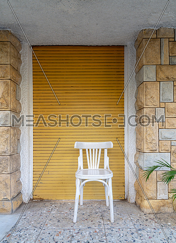 Traditional Egyptian white wooden chair over background of bricks stone wall and yellow closed roll-up door