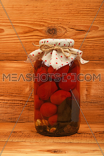 One big glass jar of homemade pickled tomatoes with dotted textile top decoration at brown vintage wooden surface