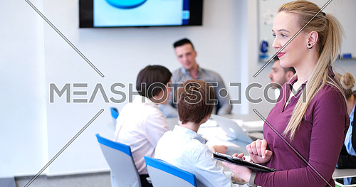 Business Woman Using Digital Tablet in Busy Office