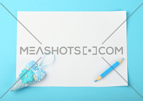 White paper note with tiny textile toy heart and small pencil on tender blue background