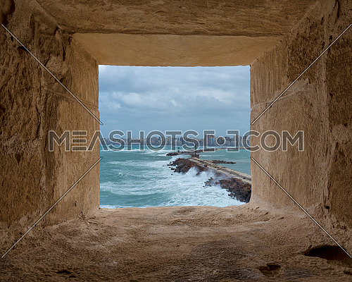 Stone window frame overlooking barrier and entrance of the old east harbor of Alexandria city at the Mediterranean Sea with skyline of the city at the far end, Egypt, includes clipping path for window