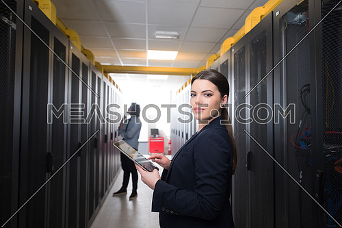 Female IT engineer working on a tablet computer in server room at modern data center