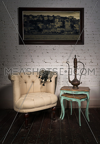 Old beige armchair,  brass teapot, hanged painting and nested ta