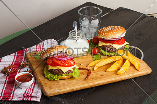 Two Burger sandwiches on a wooden tray with garnish elements