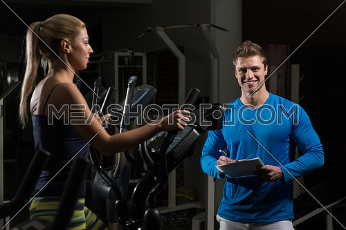 Young Woman Doing Aerobics Elliptical Walker In Gym And Personal Trainer Watching On Her