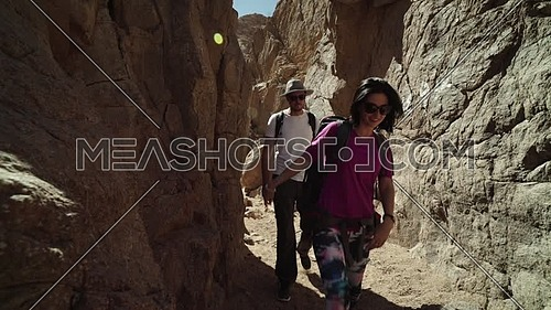 Follow shot for group of tourists go out a rocky groove while exploring Sinai Mountain for wadi Freij at day.