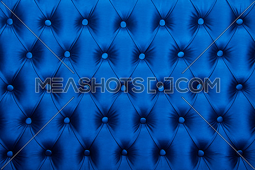 Dark blue capitone textile background, retro Chesterfield style checkered soft tufted fabric furniture diamond pattern decoration with buttons, close up