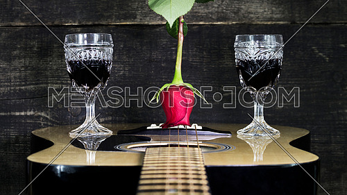 Red Rose and Wine Glasses Resting On Acoustic Guitar With Wooden Background