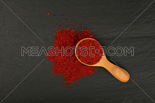Close up one wooden scoop spoon full of ground sun dried tomato or red chili pepper on background of black slate cooking board, elevated top view, directly above