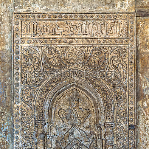 Ornate engraved stone wall with floral patterns and calligraphy at Ibn Tulun Mosque, Cairo, Egypt
