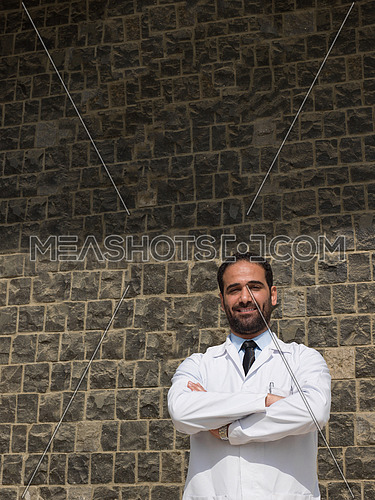 middle eastern young doctor portrait in front of modern hospital