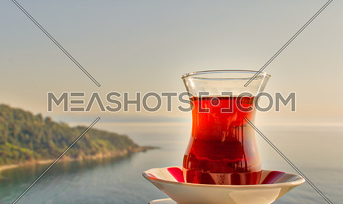 Glass of traditional Turkish tea with background of mountains of Buyukada island, Marmara sea, Istanbul, Turkey