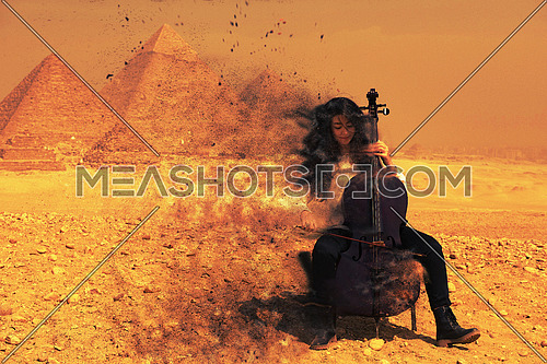 young female cello player in egyptian desert with pyramids in background