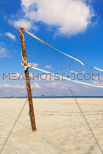 Torn volleyball net on the beach with cloudy blue sky and yellow sand in the morning