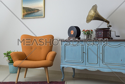 Interior of retro orange armchair, vintage wooden light blue sideboard, old phonograph (gramophone), vinyl records on background of beige wall, tiled porcelain floor, and red carpet