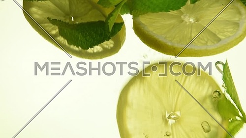 Close up several fresh green mint leaves and lemon slices thrown and floating in mojito glass, low angle side view, slow motion