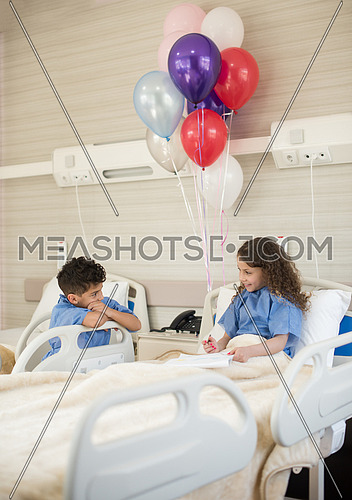little middle eastern boy and girl painting home and family at hospital bed in a large modern hospital