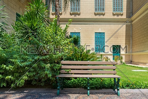 Day shot of beige garden bench at public park at summer time
