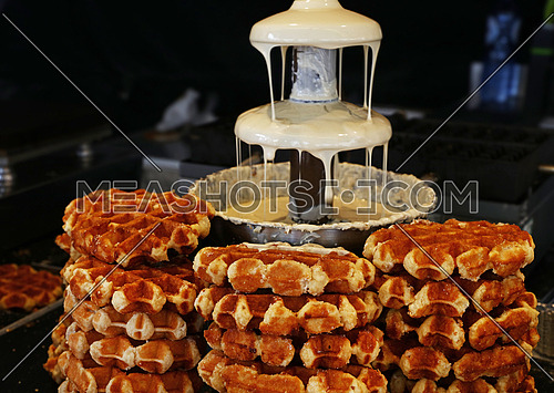 Close up of Belgian liquid white chocolate fountain for sweet fondue dip desserts and traditional wafers, low angle view