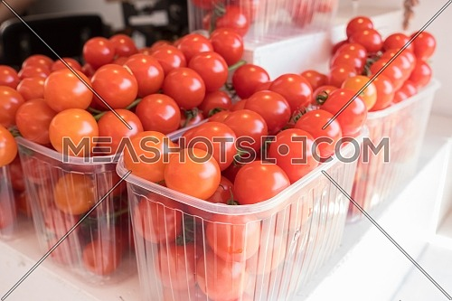baskets of small red cherry tomatoes at a sunny day outdoor farmer's market