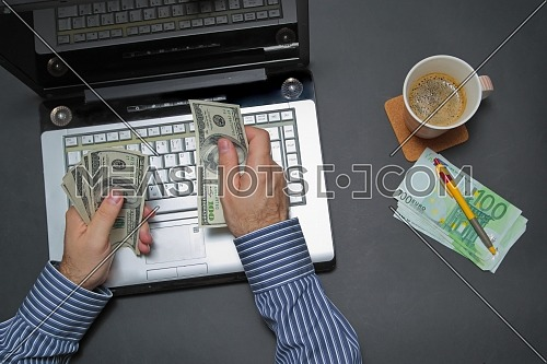 Businessman working on laptop and counting money while as he drinks coffee