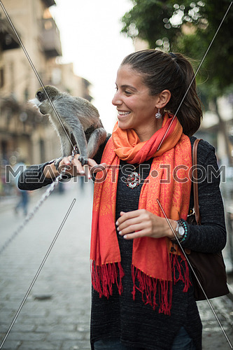 portrait of a young beautiful middle eastern woman who enjoys in the city with a monkey on her shoulder
