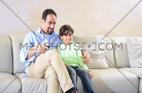 Mid shot for a male watching TV holding remot control and his son come to watch with him