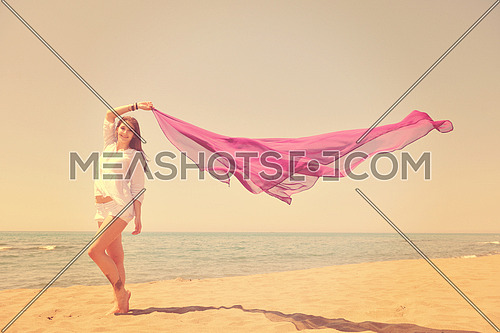 beautiful young woman on beach with scarf relax smile and have fun