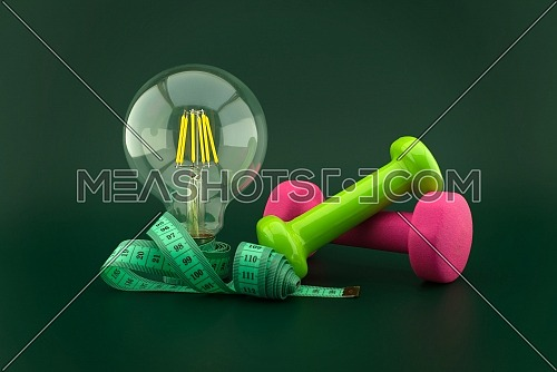 Starting weight loss and fitness idea concept with lamp light bulb, dumbbell weight and measuring tape over a dark green background