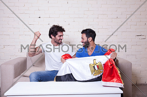 two young men sitting on a couch cheering for egypt