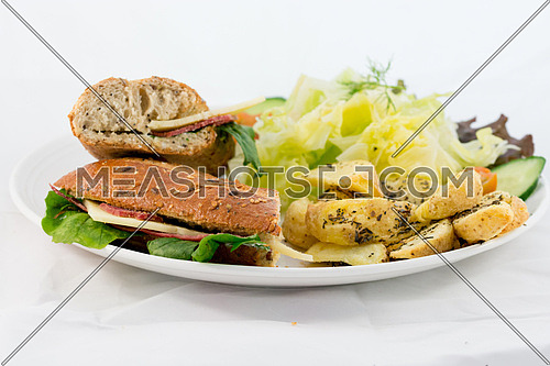 A plate with Sandwich, salad and potatoes