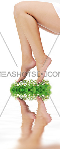 woman legs walking on small peace of green grass isolated on white representing last oasis concept