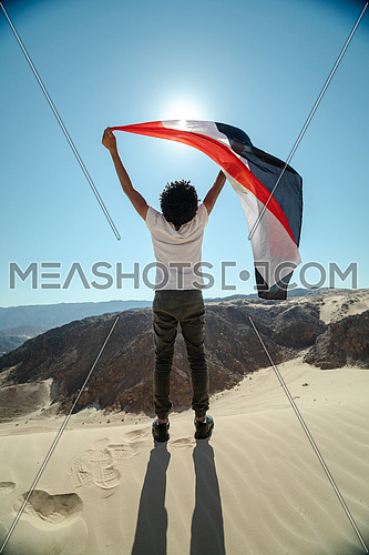 Egyptian male spreading Egyptian flag while exploring Sinai Trail from Ain Hodouda at day.