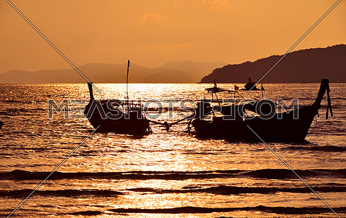 Sunset sea shore with long tail boat silhouettes and horizon over vivid sky