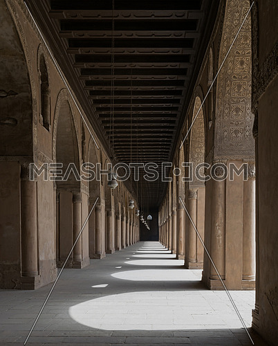 A corridor in the Mosque of Ibn Tulun with arches on both sides and hanged lanterns. The Mosque of Ahmad Ibn Tulun is the largest mosque in Cairo,  Egypt, and may be the oldest mosque in the city with its original form