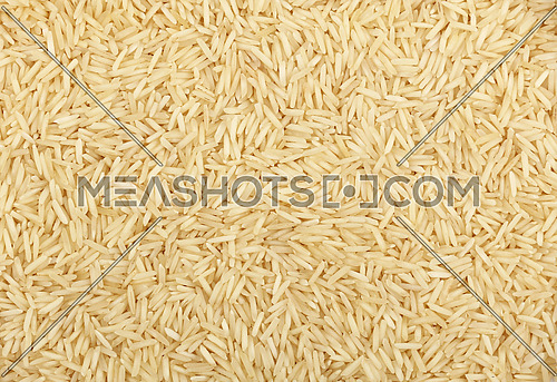 White Indian Basmati long grain rice close up pattern background, elevated top view