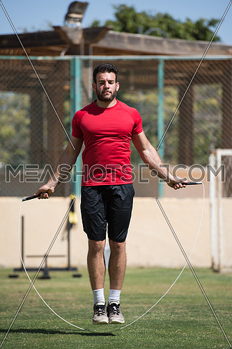 young middle eastern athlete man exercise skipping rope outdoors