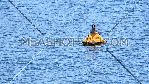 Close up yellow buoy floating in blue sea water waves and ripples