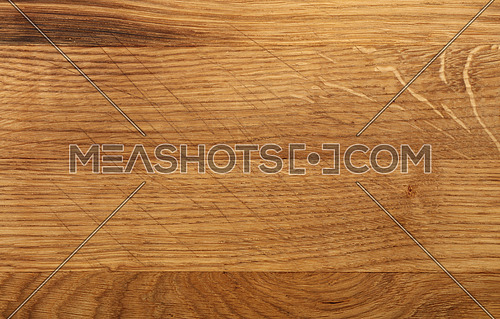Close up texture background of brown oak wood kitchen cutting board with dark burn stains and knife cut traces