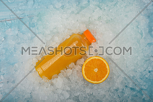Close up one plastic PET bottle of fresh orange juice and cut half orange slice over background of crushed ice, elevated high angle view, directly above