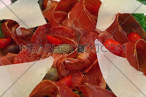 Italian antipasti plate with parmigiano cheese, smoked cured prosciutto meat, sausage and olives close up, high angle view